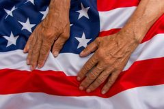 The older man put his hands on the us flag. The concept of carin. G for pensioners Royalty Free Stock Photos