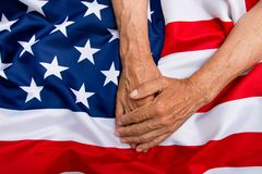 The older man put his hands on the us flag. The concept of carin. G for pensioners Stock Photos