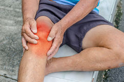 Older man puts both hands on an aching knee. Older man puts both hands on an aching knee at park royalty free stock photo