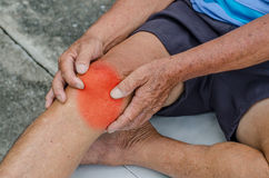 Older man puts both hands on an aching knee. Older man puts both hands on an aching knee at park stock image