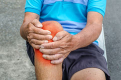 Older man puts both hands on an aching knee. Royalty Free Stock Images