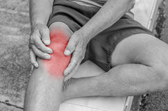 Older man puts both hands on an aching knee. Royalty Free Stock Photos