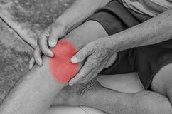 Older man puts both hands on an aching knee. Stock Image