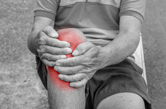 Older man puts both hands on an aching knee. Royalty Free Stock Photo