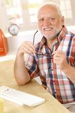 Older man putting on glasses at desk. Cheerful older man putting on glasses, sitting at desk, smiling, looking at camera Stock Photos
