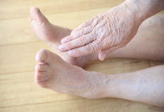 Older man reaches for his toes. A seated senior man stretches a hand toward his toes Stock Images