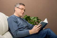 Older man reading book on sofa. Royalty Free Stock Images
