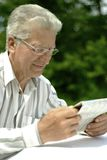 Older man reading newspaper Stock Images
