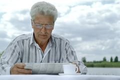 Older man reading newspaper Stock Photos