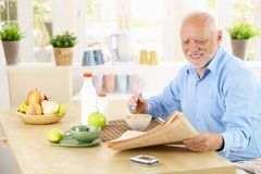 Older man reading newspaper in kitchen. While having cereal breakfast Royalty Free Stock Image