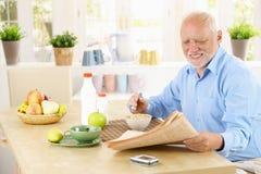 Older man reading newspaper in kitchen royalty free stock image