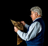 Older Man Reading Newspaper. Low key shot of older man in front of a black backdrop wearing a sweater vest and glasses and reading an old newspaper Royalty Free Stock Photos