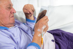 Older man receives infusion and uses a digital tablet Royalty Free Stock Photo