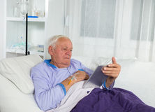 Older man receives infusion and uses a digital tablet Stock Photo