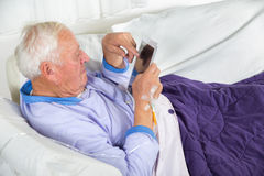 Older man receives infusion and uses a digital tablet Stock Photos