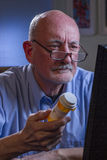 Older man refilling prescription online, vertical Royalty Free Stock Photo