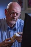 Older man refilling prescription online, vertical Royalty Free Stock Photography