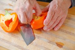 Man prepares orange bell pepper Stock Image