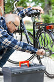 Older man repairing a bicycle Royalty Free Stock Photos