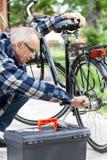 Older man repairing a bicycle royalty free stock photos