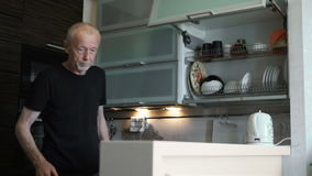 An older man retired, spends time in the kitchen of his house
