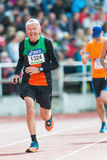 Older man running the final stretch at Stockholm Stadion. STOCKHOLM - MAY 31: Older man running the final stretch at Stockholm Stadion in ASICS Stockholm Stock Image