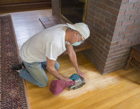 Older man sanding floor Royalty Free Stock Photos