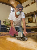 Older man sanding floor Stock Photography