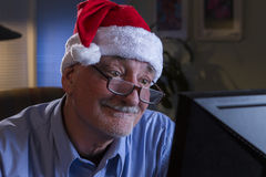 Older man in Santa hat looking happy and nostalgic, horizontal Royalty Free Stock Images