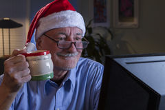 Older man in Santa hat looking happy and nostalgic, horizontal Royalty Free Stock Image