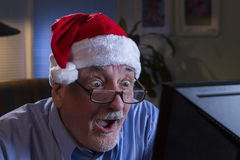Older man in Santa hat looking shocked, horizontal Stock Images