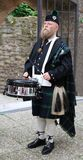 Older man, Scottish, with long beard and kilt, plays on a drum, and drumsticks, he has fu
