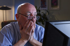 Older man shocked with content on his computer, horizontal Royalty Free Stock Images