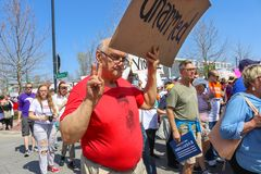 Older man with sign that says Unarmed living peace sign in front of many marchers at March for Life protest Tulsa Oklahoma USA 3 2. An Older man with sign that Stock Images