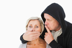 Older man silencing his fearful partner Royalty Free Stock Image