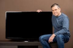 Older man sitting and holding tv set. Stock Photos