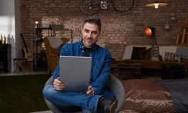 Older man sitting at home using tablet. Happy older white man with gray hair in casual jeans sitting at home using tablet, working Royalty Free Stock Photography