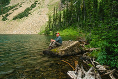 Older Man Sitting on a Rock Fishing a High Mountain Lake Royalty Free Stock Photography