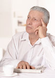 Older man sitting at a table at home Royalty Free Stock Images
