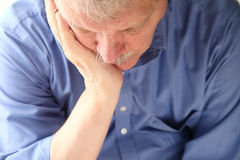 Older man slumped in depression. Unhappy senior man slouches with face in hand Stock Photos