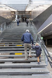 Older man and small girl climb stairs to utrecht central railway Stock Image