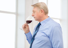 Older man smelling red wine. Alcohol and beverage concept - older man smelling red wine Royalty Free Stock Image