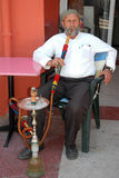 The older man smokes a hookah Royalty Free Stock Photography