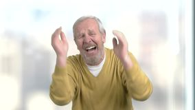 Older man suffering in despair. Senior desperate man crying and gesturing with hands on blurred background, slow motion. Hopeless face expression stock video