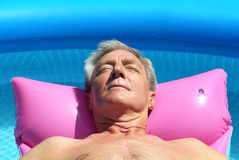 Older man sunbathing on a lilo. Older man floating on a pink lilo and sunbathing in a swimming pool Stock Image