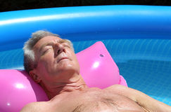 Older man sunbathing on a lilo. Older man floating on a pink lilo and sunbathing in a swimming pool Royalty Free Stock Photography