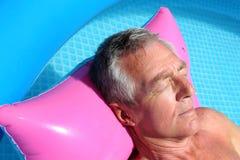 Older man sunbathing on a lilo. Older man floating on a pink lilo and sunbathing in a swimming pool Stock Photos