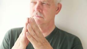 Older man taps fingers together stock video