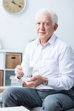Older man and tea time. Senior elegant happy man drinking tea in afternoon. Sitting on a chair at home stock image