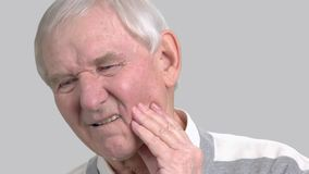 Older man with the tooth pain, toothache. Male senior suffering from terrible toothache on grey background. Sick old man stock video footage